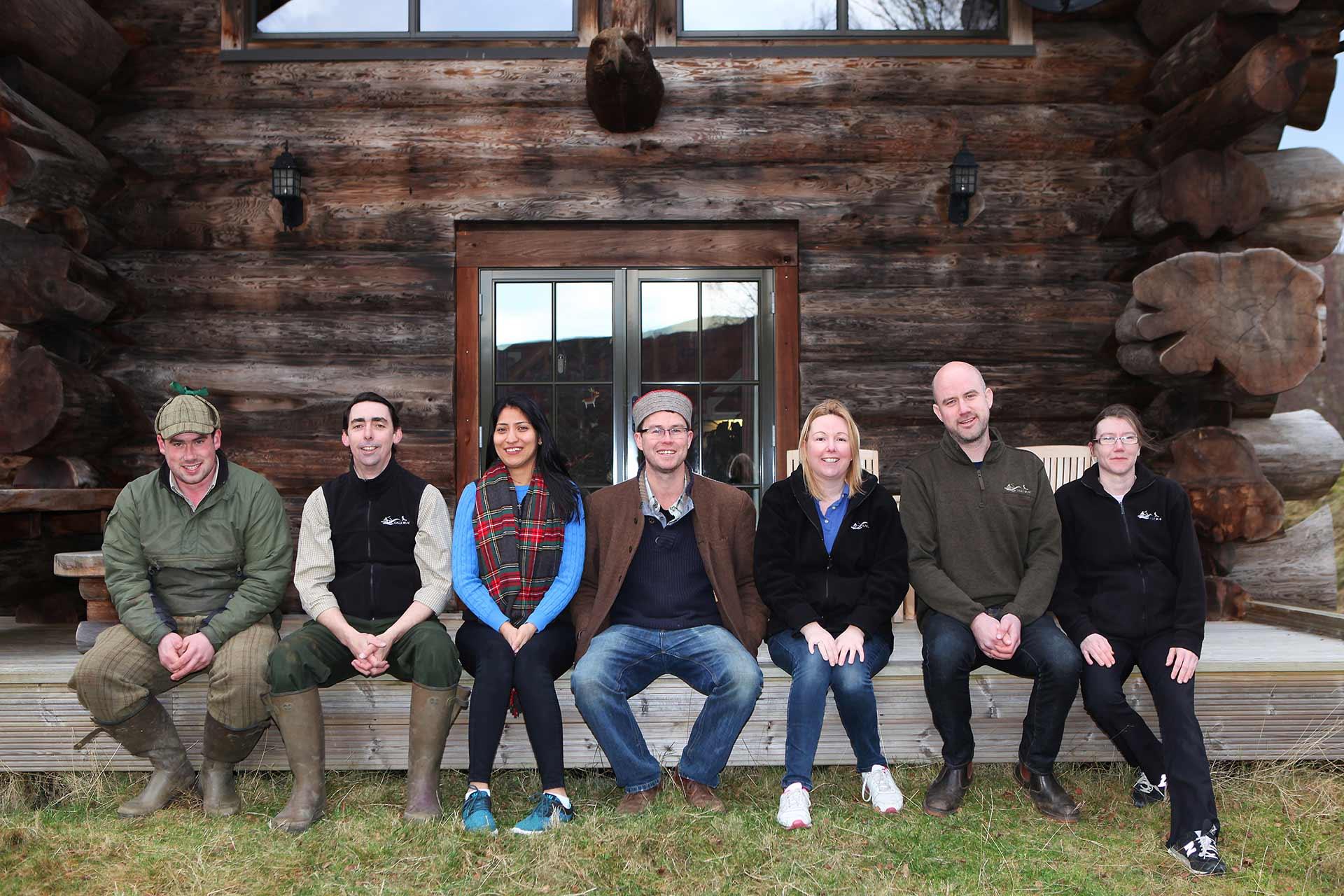 Eagle Brae team sat outside a log cabin