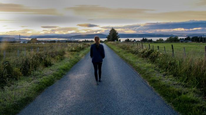 Woman walking along road Beauly Scotland